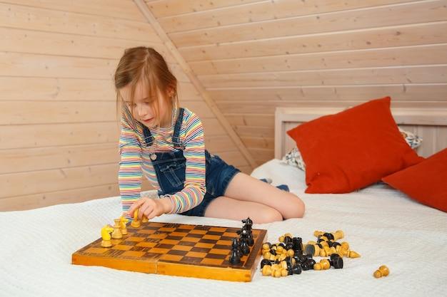 Kleines mädchen legt stücke auf ein schachbrett. schachspiel Premium Fotos