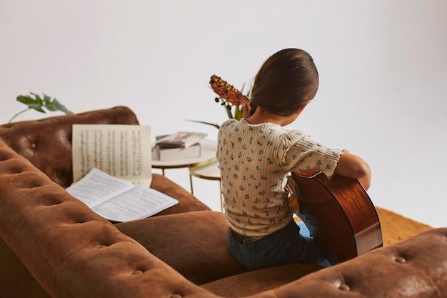 Kleines mädchen lernt, wie man zu hause gitarre spielt Kostenlose Fotos