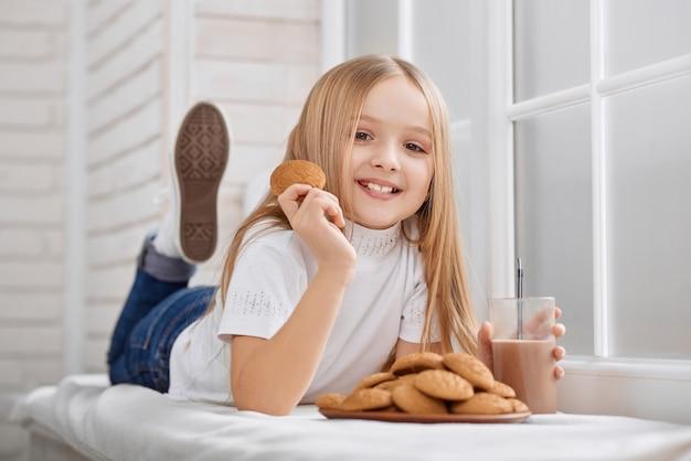 Kleines mädchen liegt auf dem fensterbrett mit keksen und schokoladenmilch Premium Fotos