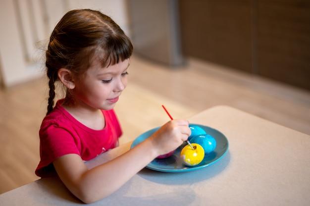 Kleines mädchen malt ostereier auf blauem teller, der am tisch in der küche sitzt Premium Fotos