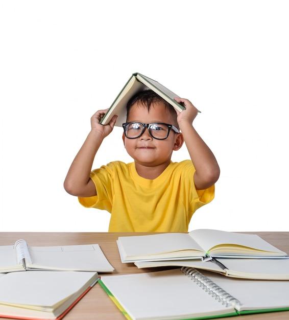 Kleines mädchen mit brille dachte und viele bücher auf dem tisch. zurück zu schulkonzept, isoliert auf weiss Premium Fotos
