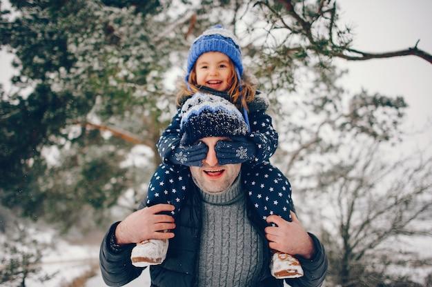Kleines mädchen mit dem vater, der in einem winterpark spielt Kostenlose Fotos
