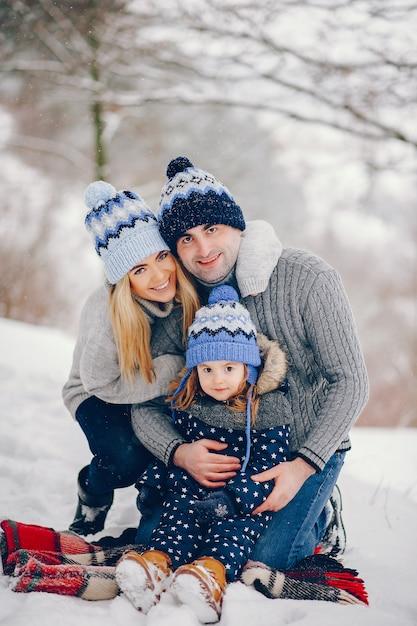 Kleines mädchen mit den eltern, die auf einer decke in einem winterpark sitzen Kostenlose Fotos