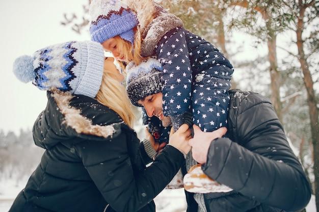 Kleines mädchen mit den eltern, die in einem winterpark spielen Kostenlose Fotos