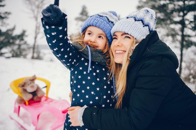 Kleines mädchen mit der mutter, die in einem winterpark spielt Kostenlose Fotos