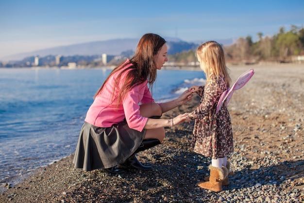 Kleines mädchen mit der mutter, die spaß auf dem strand an einem wintertag hat Premium Fotos
