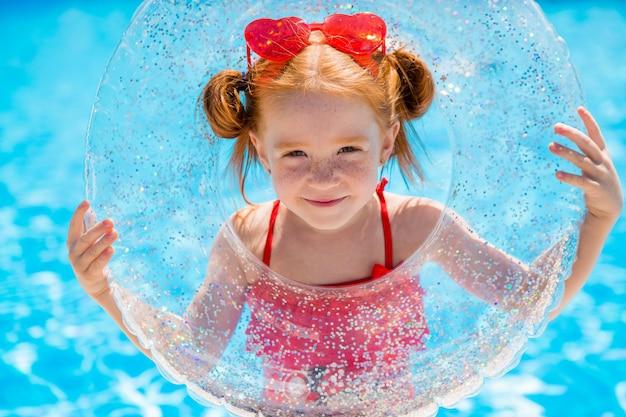 Kleines mädchen mit einem schwimmkreis im pool Premium Fotos