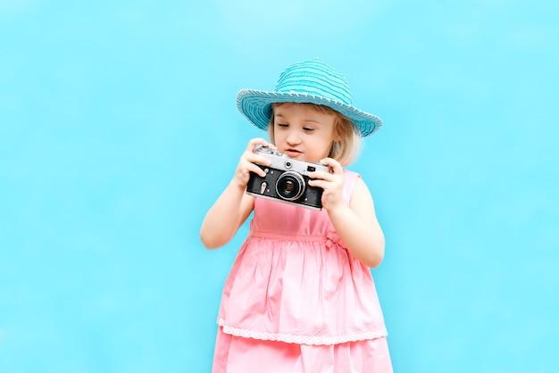 Kleines mädchen mit einer kamera in der hand im studio Premium Fotos
