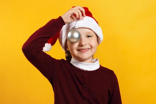 Kleines mädchen mit einer weihnachtskugel Premium Fotos