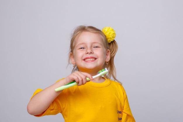 Kleines mädchen mit einer zahnbürste, kleines mädchen mit einer zahnbürste und einem apfel. Premium Fotos