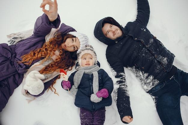 Kleines mädchen mit eltern in einem winterpark Kostenlose Fotos