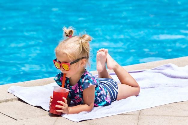 Kleines mädchen mit frischem cocktail auf swimmingpool am sommertag Premium Fotos