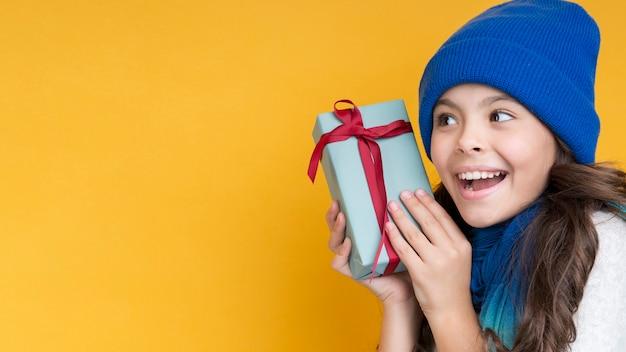 Kleines mädchen mit geschenkkopieraum Kostenlose Fotos