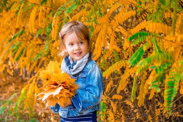 Kleines mädchen mit goldenen blättern des gelben herbstes. kinderspiel draußen im park. Premium Fotos