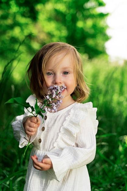 Kleines mädchen mit grünen augen in einem grünen garten mit einer lila blume schaut in den rahmen Premium Fotos