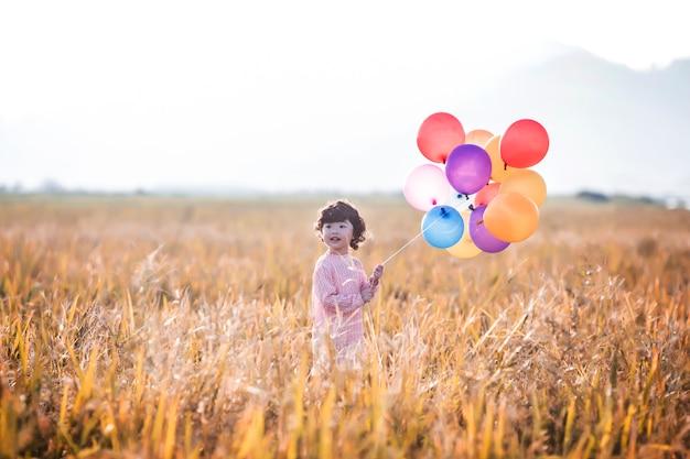 Kleines mädchen mit luftballons auf weizenfeld spielen Kostenlose Fotos