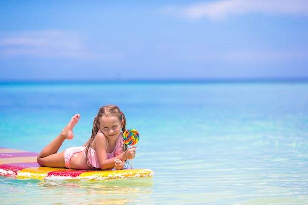 Kleines mädchen mit lutscher haben spaß auf surfbrett im meer Premium Fotos
