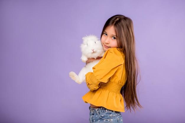 Kleines mädchen mit osterhasen auf lila hintergrund Premium Fotos