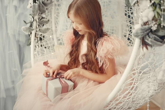 Kleines mädchen nahe weihnachtsbaum in einem rosa kleid Kostenlose Fotos