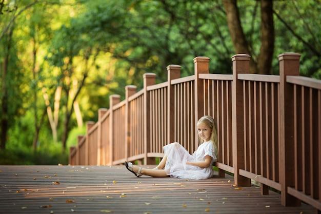 Kleines mädchen sitzt auf der brücke im park Premium Fotos