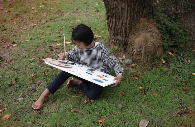 Kleines mädchen sitzt auf grünem gras im erdgeschoss und malt farbe auf leinwand. mit glücklichem gefühl, gutem hobby, in einem park Premium Fotos