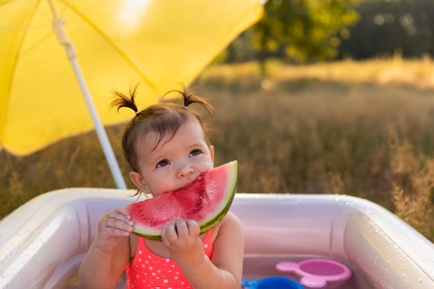 Kleines mädchen spielt im aufblasbaren pool. Premium Fotos