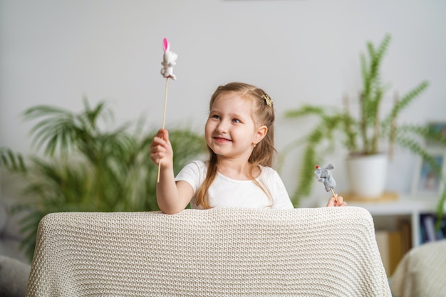 Kleines mädchen spielt theater. fingerpuppen gekleidet auf stöcken, die von einem kind gehalten werden Premium Fotos