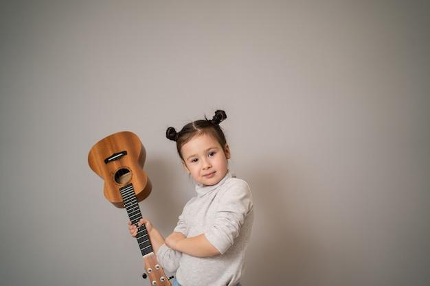 Kleines mädchen spielt ukulele. kreative entwicklung bei kindern. musikalische ausbildung von kindheit an. musik online zu hause unterrichten. Premium Fotos
