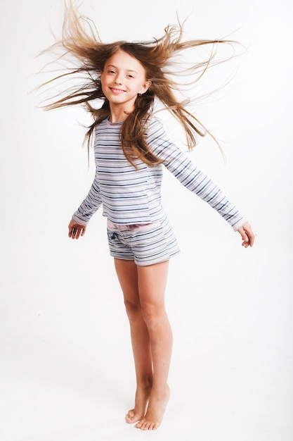 Kleines mädchen springen über weiß Premium Fotos
