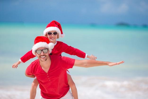 Kleines mädchen und glücklicher vater in santa hat während der strand weihnachtsferien Premium Fotos