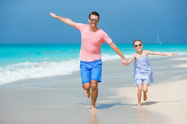Kleines mädchen und glücklicher vati, die spaß während der strandferien hat Premium Fotos