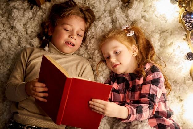 Kleines mädchen und junge lesen ein buch in einem dekorierten raum für weihnachten. Premium Fotos