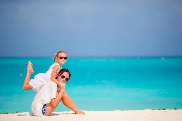 Kleines mädchen und junge mutter während der strandferien Premium Fotos
