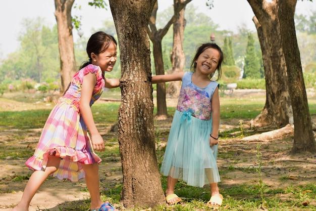 Kleines mädchen und seine schwester spielen im sommerpark Premium Fotos