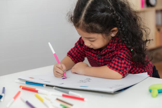 Kleines mädchen und zeichnungsspaß auf dem papierweiß Premium Fotos