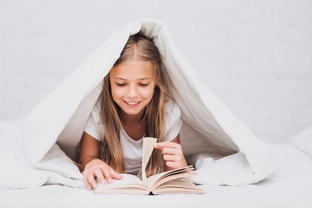 Kleines mädchen unter der decke ein buch lesend Kostenlose Fotos