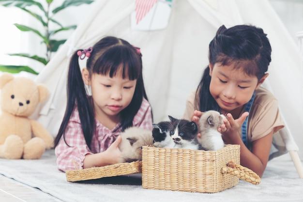 Kleines mädchen zwei, das zu hause mit katze, freundschiffskonzept spielt. Premium Fotos