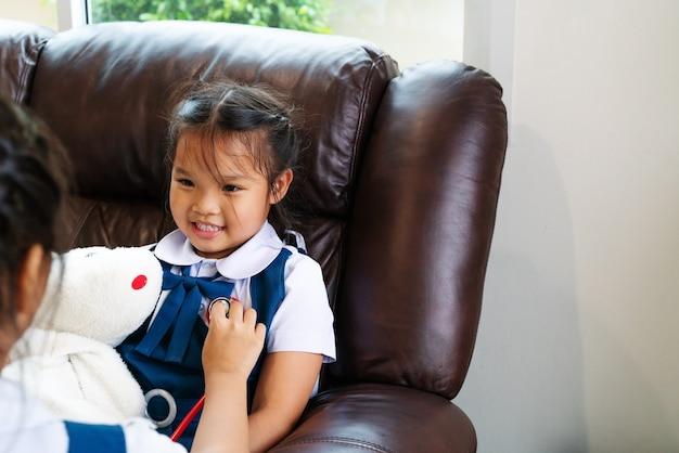 Kleines mädchen zwei lächeln und doktor mit stethoskop spielend. Premium Fotos