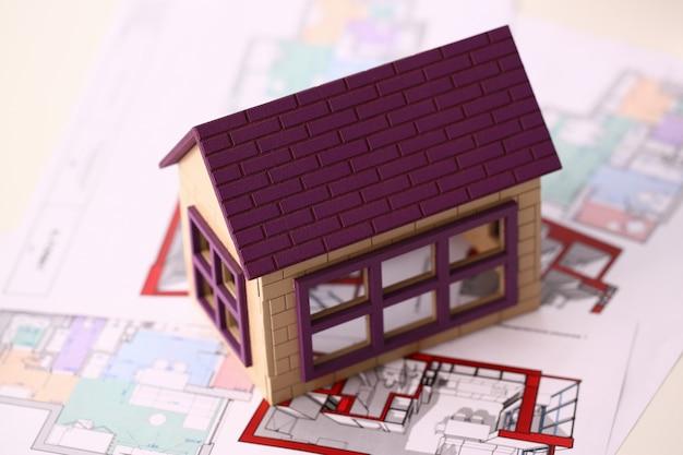 Kleines miniaturhaus steht auf zeichnung Premium Fotos