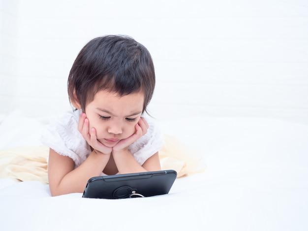 Kleines nettes mädchen, das auf weißem boden liegt und smartphone mit ernsthaft aufpasst. Premium Fotos