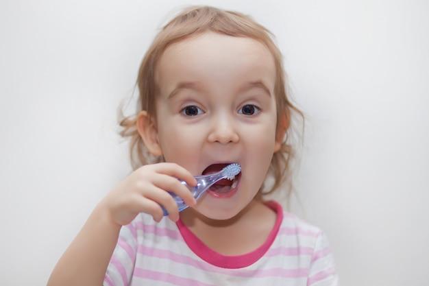 Kleines nettes mädchen, das ihre zähne smailing und putzt. Premium Fotos