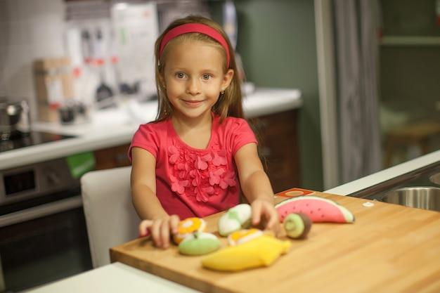 Kleines nettes mädchen, das in der küche mit obst und gemüse spielt Premium Fotos