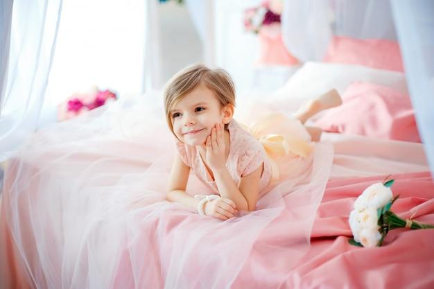 Kleines nettes mädchen im kleid, das auf bett mit blumen liegt Premium Fotos