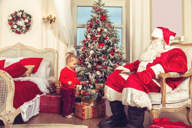 Kleines nettes mädchen mit einem wirklichen weihnachtsmann nahe dem weihnachtsbaum. Premium Fotos