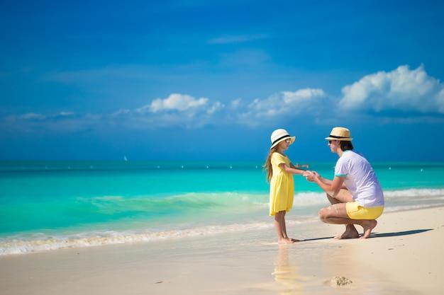 Kleines nettes mädchen und ihr vater auf tropischem exotischem strand Premium Fotos