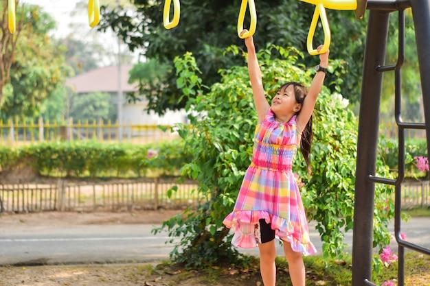 Kleines nettes mädchen, welches die stange am park hängt. training lernfähigkeit, übung. Premium Fotos