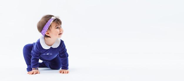 Kleines nettes neugieriges entzückendes lächelndes mädchen mit bogen im kriechenden sitzen des haares im studio, das auf weißem hintergrund aufwirft Premium Fotos