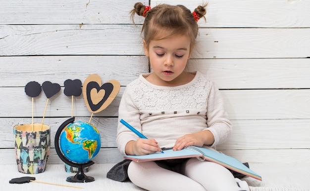 Kleines niedliches mädchen schulmädchen sitzt auf einem weißen hölzernen hintergrund mit einem globus in seinen händen und einem notizbuch, das konzept des wissens Kostenlose Fotos