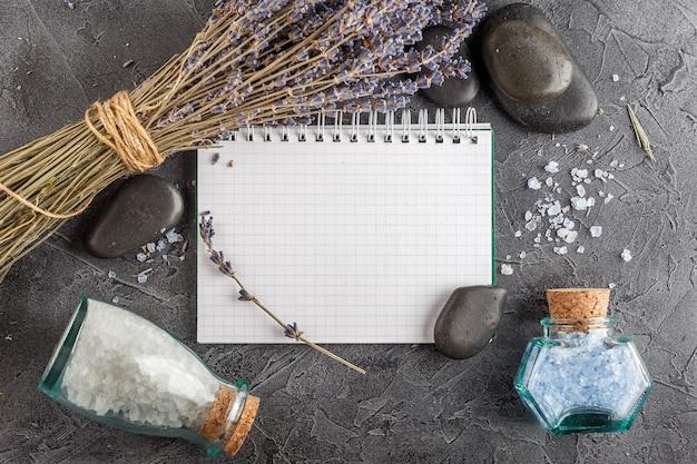 Kleines notizbuch, lavendel, mineralisches meersalz und zensteine auf grauem steinhintergrund. draufsicht. Premium Fotos
