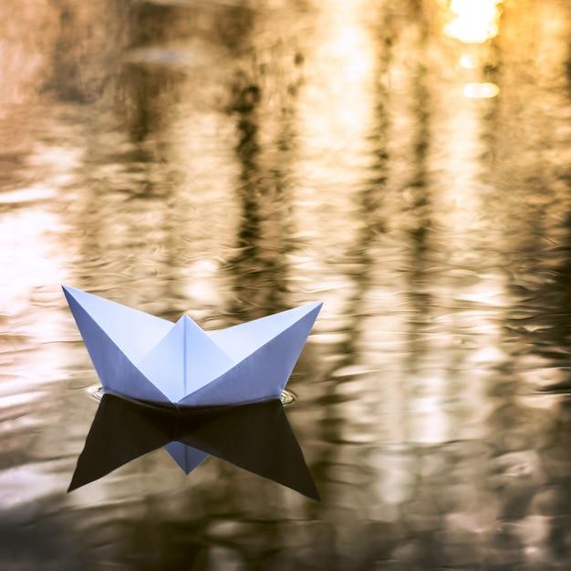 Kleines papierboot, das hinunter den fluss im herbst bei sonnenuntergang segelt. konzept der einsamkeit, verlassenheit Premium Fotos
